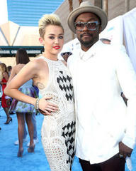 Miley Cyrus cosies up to Will.i.am for backstage pic